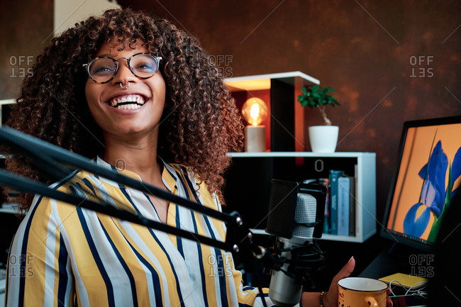 Young Afro American artist podcasting with a microphone in front of her computer