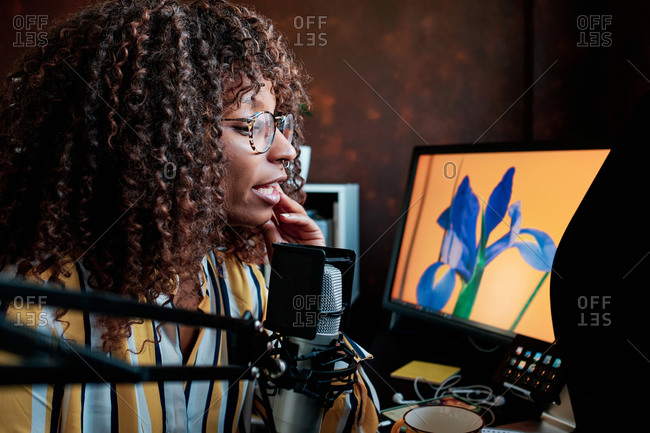 Afro American artist podcasting with a microphone in front of her computer