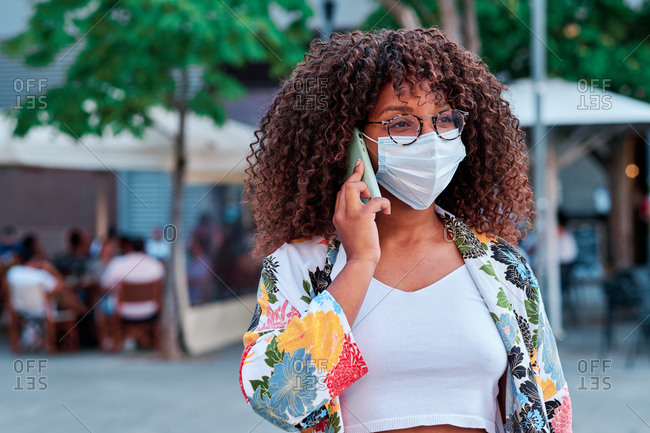 Afro American woman using mobile phone and wearing a face mask during coronavirus outbreak