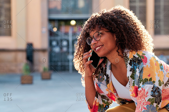 Young Afro American woman with curly hair using her mobile phone outdoors in the sunshine
