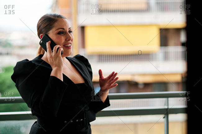 Young curvy female executive using a mobile phone on a balcony with city background