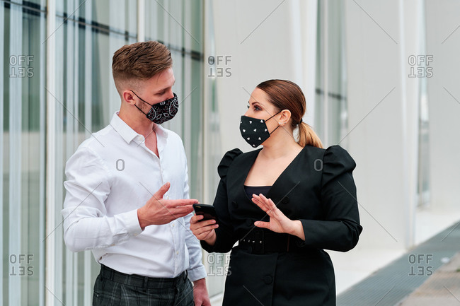 Two executives wearing face masks outside a building during coronavirus outbreak