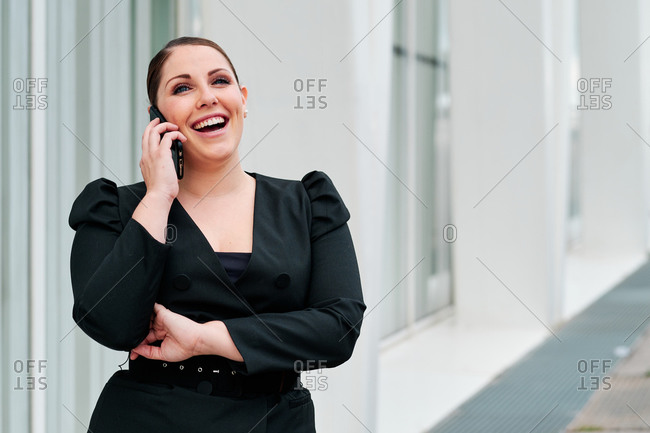 Young curvy female executive using mobile phone on the streets of the city