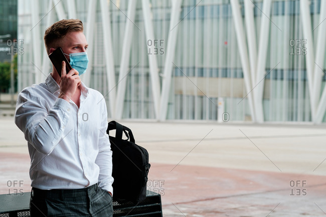 Young executive man wearing a face mask to prevent coronavirus and using a mobile phone