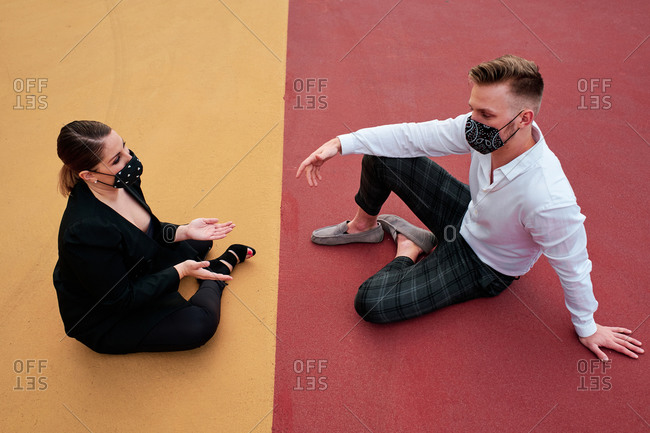 A young guy and a curvy woman with face mask sitting on the ground outside their office talking