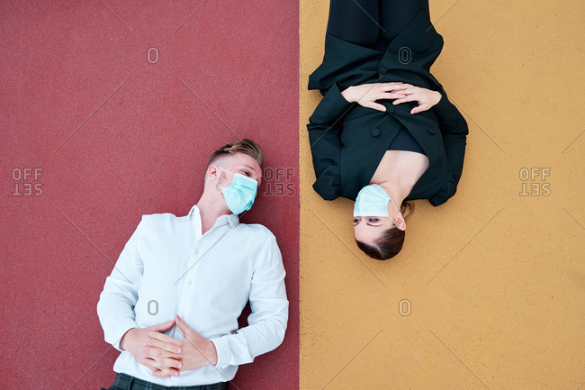A young guy and a curvy woman with face mask lying on the ground outside their office talking