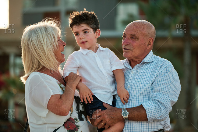 Young boy with grandparents in a sunny day