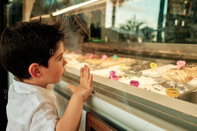 A little child showing desire for different ice creams in a case
