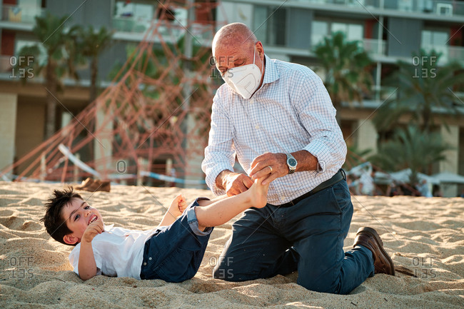Grandfather with face mask during coronavirus outbreak tickles his grandson at the beach