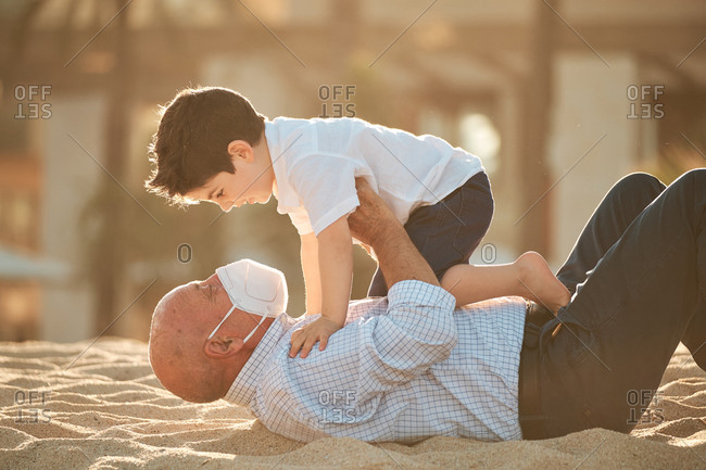 Grandfather with face mask during coronavirus outbreak plays with grandson at the beach