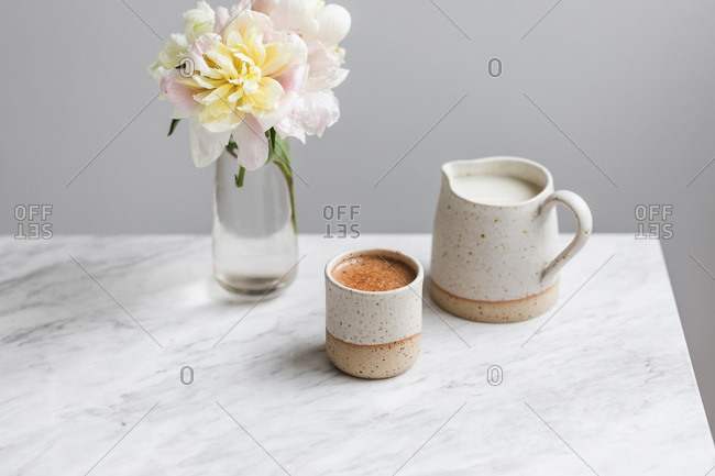 Cup of coffee and a jug of milk on a white marble table
