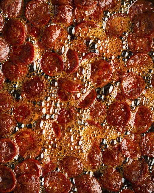 Chorizo frying in oil studio shot
