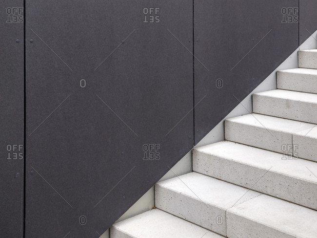 Modern cement stairway against slate wall