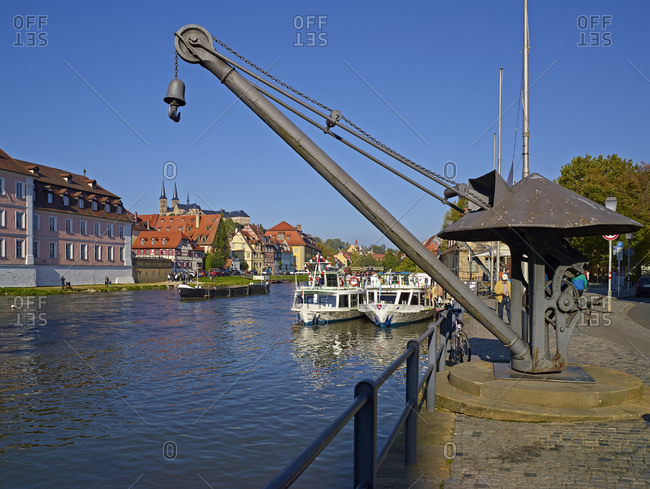 September 28, 2013: Old load crane and excursion boats on the Regnitz in Bamberg, Upper Franconia, Bavaria, Germany