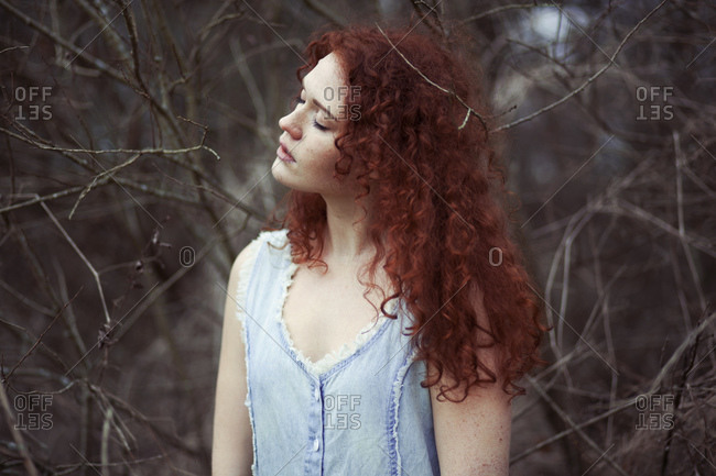 Woman with long red hair between branches, portrait