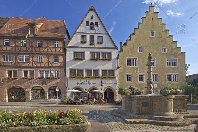 July 18, 2014: Gothic house in Herrngasse with Herrnbrunnen in Rothenburg ob der Tauber, Bavaria, Germany