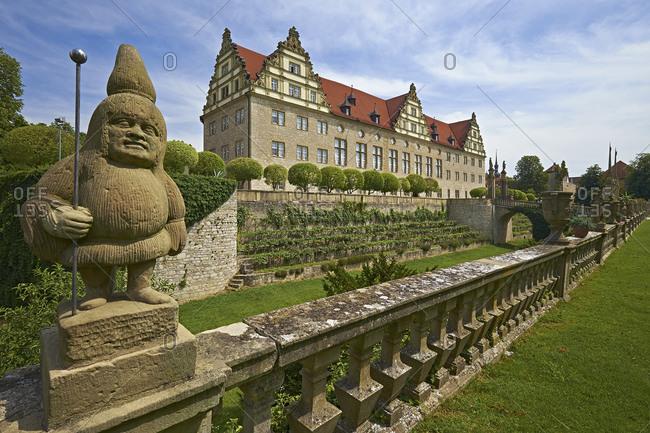 July 20, 2014: Sandstone figure with Weikersheim Castle, Main-Tauber-Kreis, Baden-Wurttemberg, Germany