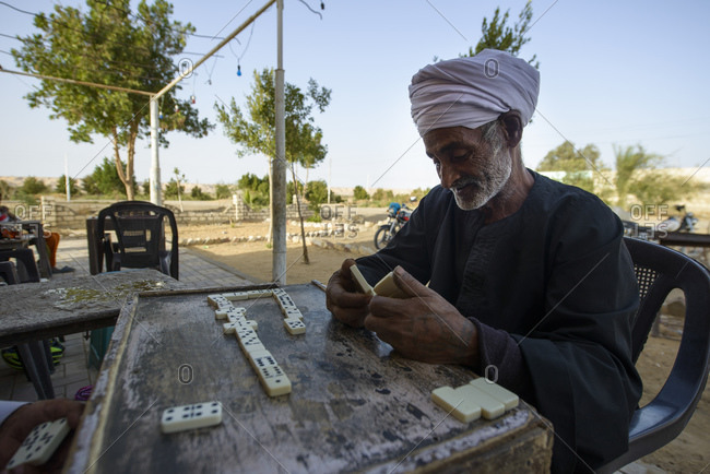 March 31, 2014: Sahara desert men play dominoes in front of a tea house in an oasis, Egypt