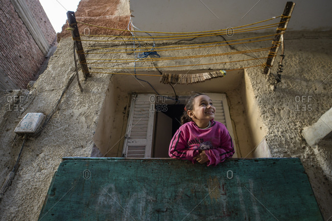 March 16, 2014: Little girl looks out the window in Cairo's old quarter, Egypt