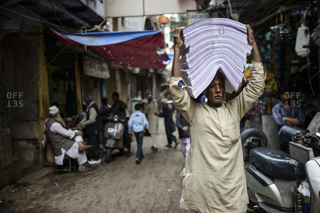 March 11, 2014: Man carries piles of paper through the streets of Old Delhi, India