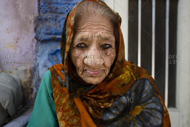 March 6, 2014: Old woman sitting on the floor outside her house, Jodhpur, India