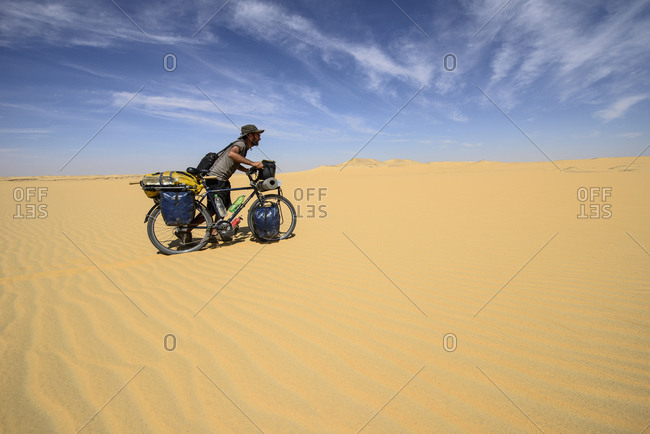 April 6, 2014: Man pushes bike over the sand dunes of the Sahara, Egypt