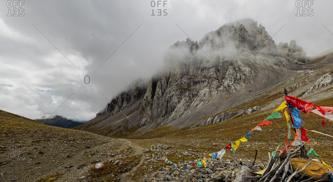 Remote mountain pass on the Tibetan plateau, indicated by Tibetan prayer flags, in Sichuan province, China