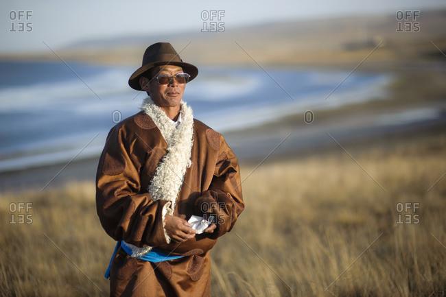 October 3, 2012: Tibetan man on the bank of Qinghai Lake on the Tibetan Plateau, Qinghai Province, China