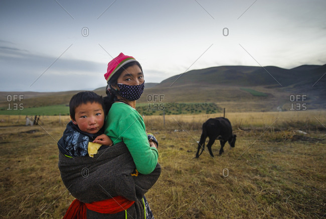 October 9, 2012: Tibetan mother carries her son in a cloth in the field, Tibetan Plateau, Gansu Province, China