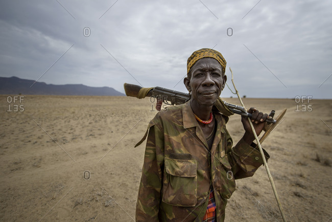 August 2, 2014: A Turkana warrior walks through the desert to protect his herd of goats, Kenya