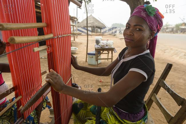 December 4, 2015: Girls and women work on their looms in a village in northern Benin, Africa