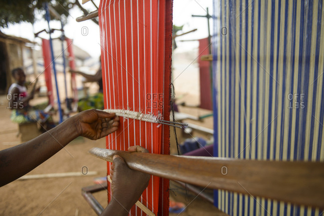 Girls and women work on their looms in a village in northern Benin, Africa