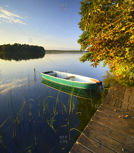 Jetty with fishing boat in the evening light, Grosser Lychensee, Uckermark, Brandenburg, Germany