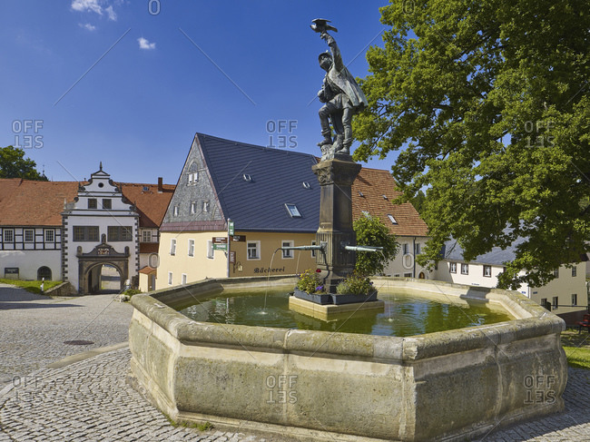 August 18, 2016: View over the market to the castle with falconer fountain, Lauenstein, Erzgebirge, Saxony, Germany