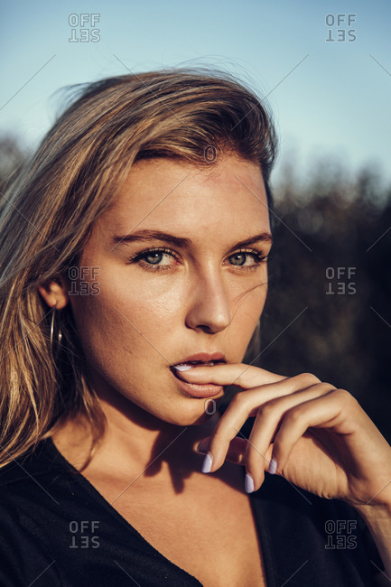 Close-up of a pretty blonde woman with blue eyes looking at camera while biting her finger at sunset