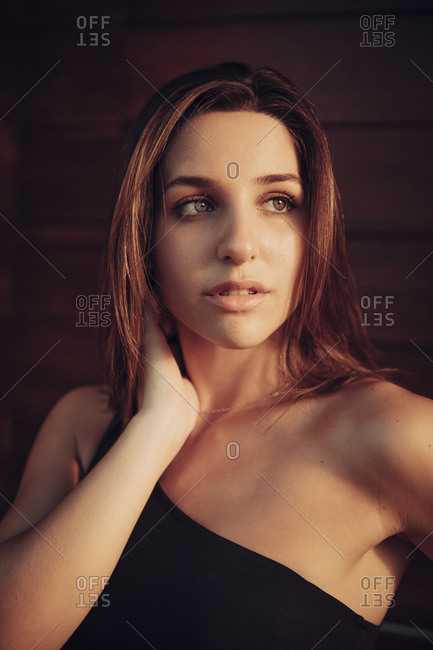 Portrait of a brunette woman with brown eyes touching her neck