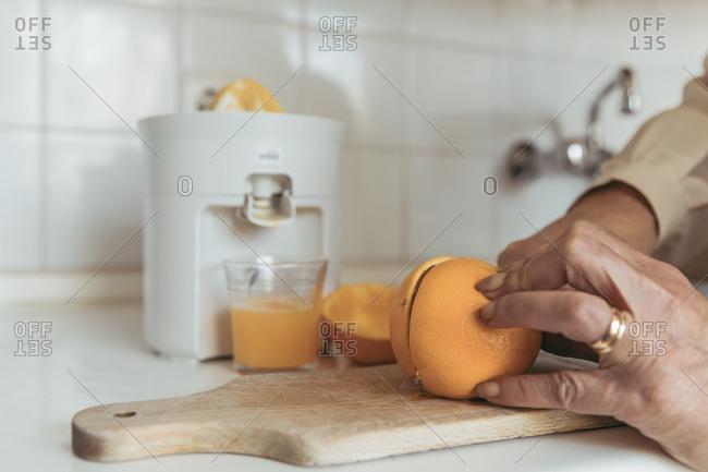 Close-up of a woman's hands by squeezing an orange with a juicer