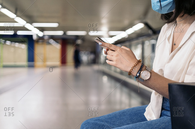 Woman wearing a mask while sitting on a metro platform checking the schedules on her phone