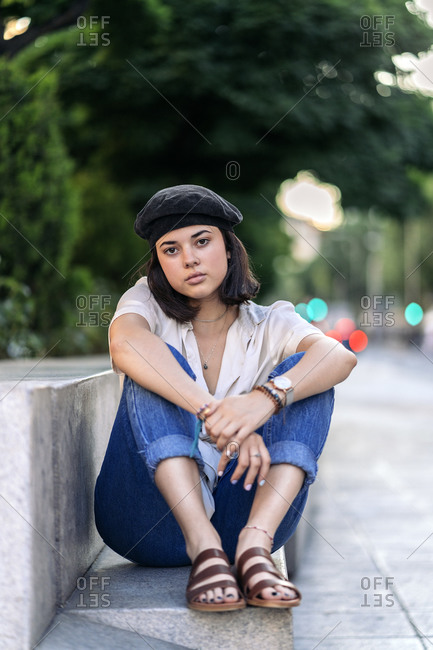 Young woman posing and looking at camera on a bench in the street