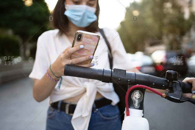 Short-haired woman using her phone on the street to unlock a public scooter while wearing a facemask