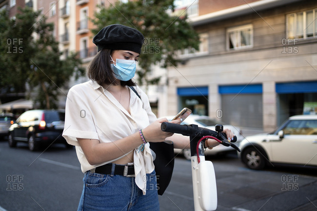 Beautiful young woman using her phone on the street to unlock a public scooter while wearing a facemask