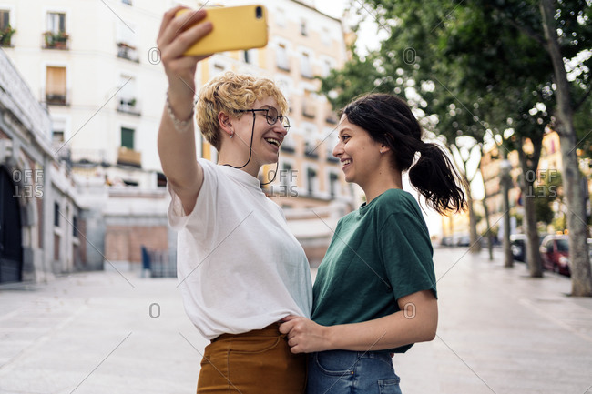 Lesbian couple smiling and taking a selfie while looking at each other