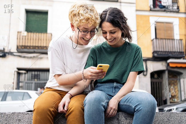 A lesbian couple using a smartphone while seated in the street together