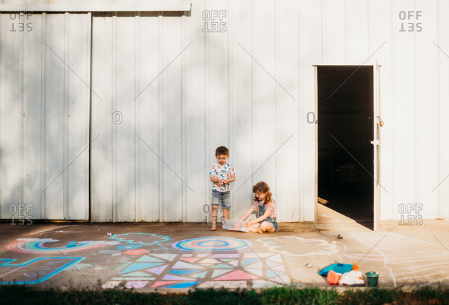 Two young kids coloring with chalk on sidewalk