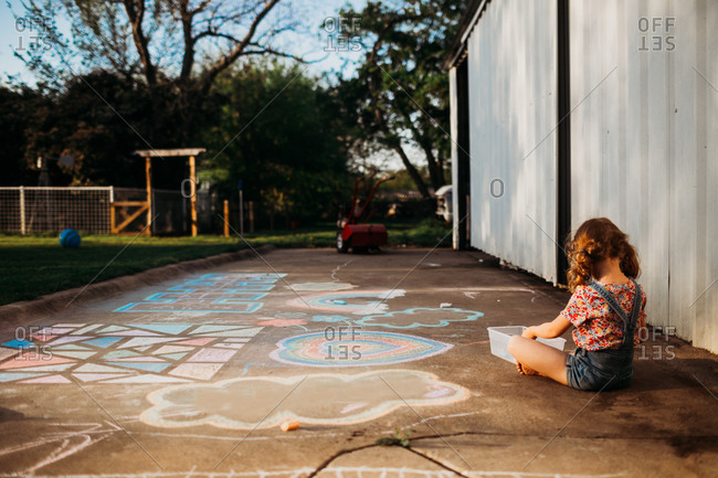 Young girl making colorful art with chalk