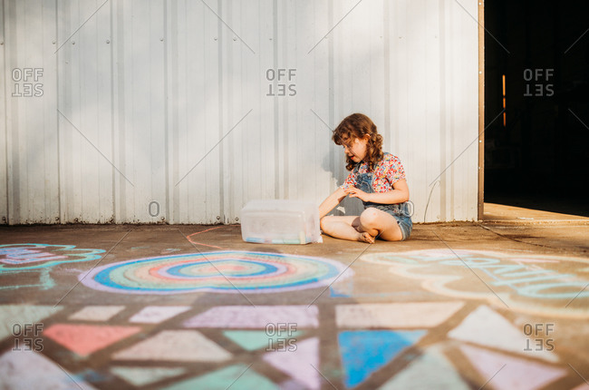 Young girl outside coloring with chalk on sidewalk