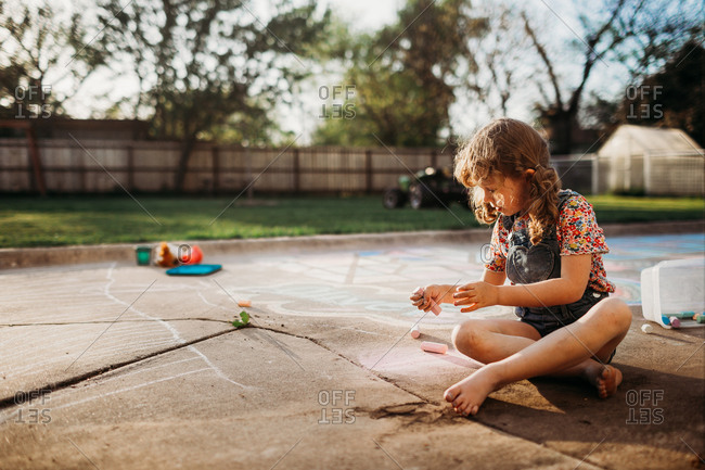 Preschool age girl coloring with chalk at sunset