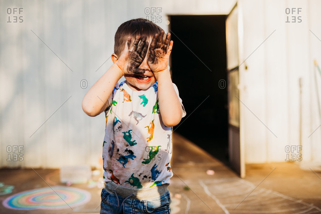 Toddler boy smiling at camera with messy hands covering his face