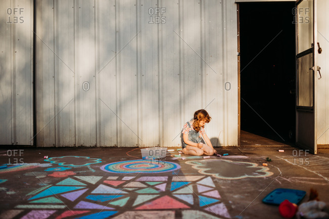 Young girl coloring with chalk in back yard at sunset
