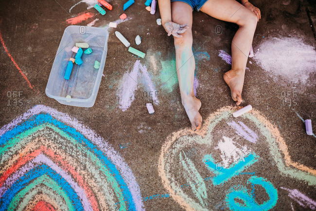 Overhead view of young girl coloring with chalk